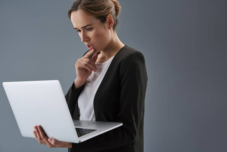 Waist up portrait of confused woman in formalwear isolated on gray background. She holding laptop in hands and looking at monitor.