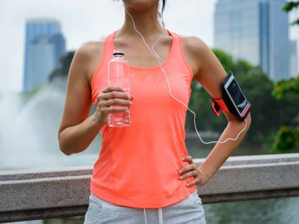 Sweaty woman drinking water during outdoor fitness workout rest. Female runner taking a running break.