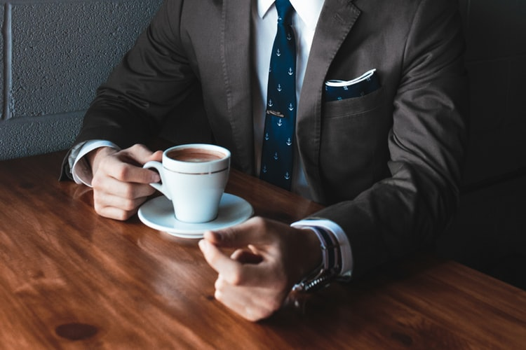 Uhr am Handgelenk eines Kaffee trinkenden Geschäftsmanns